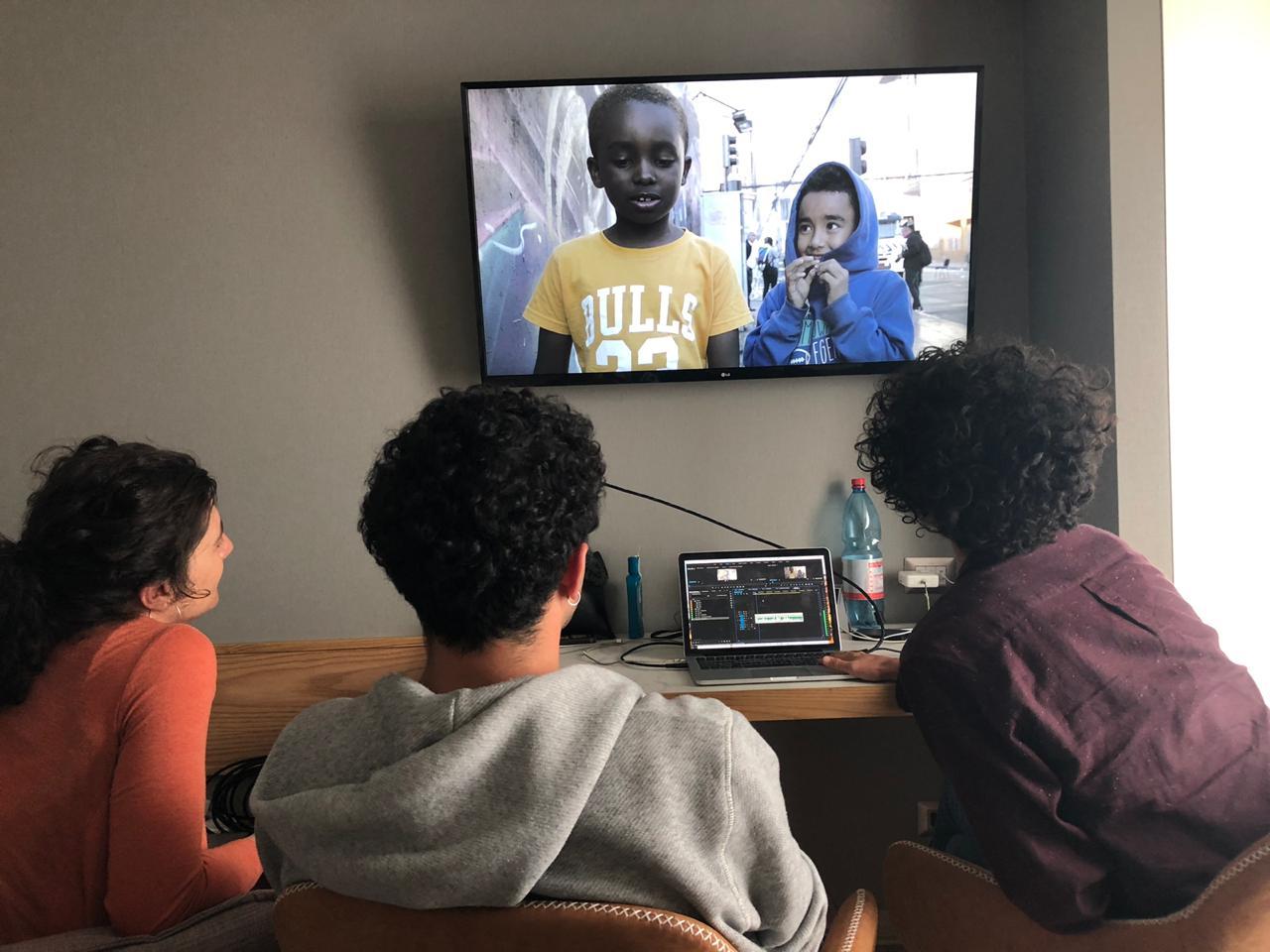 Tres jóvenes viendo una muestra audiovisual del Festival en la televisión
