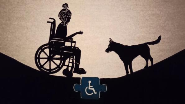 """Fotograma del cortometraje """"Como pez en el agua"""". Títere de una niña en silla de ruedas cruzando de un lado a otro gracias a la accesibilidad, junto a la ayuda de su perro."""